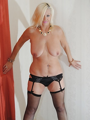 Platinum blond strips over her panties to reveal her shaved mature pussy.
