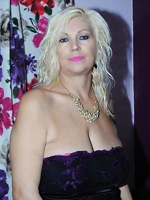 Platinum blond dressed in black dress pink panties and fishnet tights, flashing her E cup mature tits.