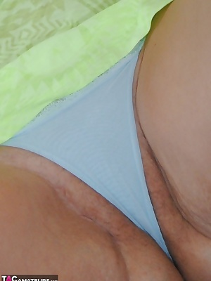 Pictures of The English Lady in her bright green top bra and panties stripping naked to reveal her wet pussy and DD tits