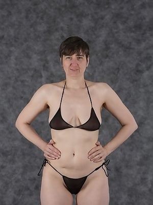 in black bikini in photo studio. Slowly I leave top and panties fall.
