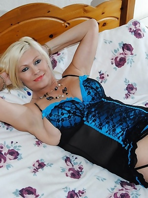 More Pictures of Platinum Blonde in blue lingerie showing her mature DD tits.