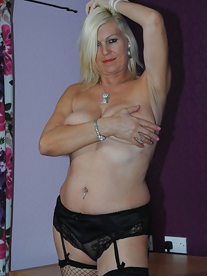 Pictures of Platinum Blonde in her short black skirt and underwear stripping of to show her sexy DD tits and shaved puss