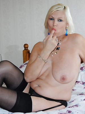 Pictures of Platinum Blonde just in stockings and suspender showing her DD tits and shaved pussy.