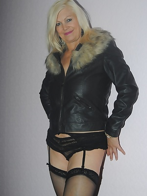 Platinum Blonde is wearing only her leather fur trimmed coat, black panties and stockings. Slowly she strips of her jack
