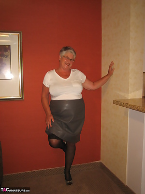 Girdlegoddess in a leather skirt and tight white top. Cum have a look at my upskirt shots with my black stockings and ho