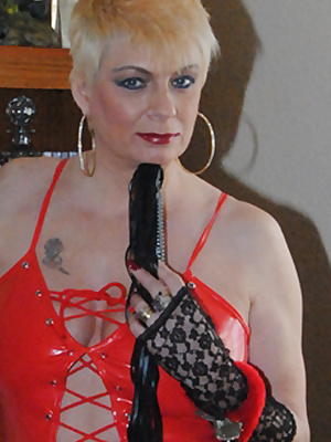 Mistress Di is dressed in red PVC and has her whip and handcuffs ready. For your pleasure she flashes her tits and pussy