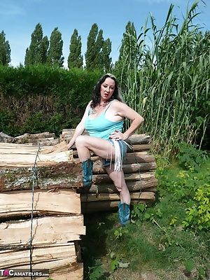 Dressed with shorts and cowboy boots on a woodpile, I show my big tits, I masturbates and fingering my pussy and I pee.