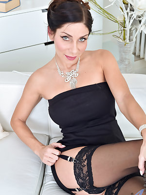Dressed to impress in a tight evening gown, Rachel Evans is a sleek lady. Once she starts peeling off her dress, though, this freak between the sheets is all about playing with her huge enhanced breasts and teasing her bald cunt as she chases the sheer pl