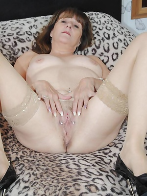 Pam strips off fully showing off her pirced pussy while sliding her dildo into it.