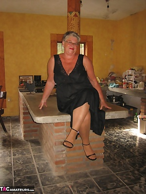 Girdlegoddess, in her sexy black lingerie and heels, standing on the counter top hugging the pillar and giving you all h