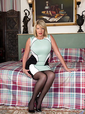 54 year old Amy Goodhead is a British mom with attitude! Her big ass and landing strip fuck hole are barely covered by a thong, and her big boobs want to bust right out of their bra. Check her out as she gets down to her garter belt and thigh highs and pr