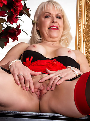 Dressed in a form fitting sheer dress, Margaret Holt is a stunning blonde you'll want to fuck. Don't miss this busty granny as she shows off her enhanced knockers and her juicy landing strip snatch that is slippery with her creamy nectar as she dreams of