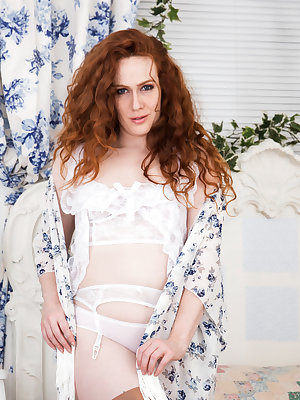Mature mom Annie M. is a curvy redhead wearing sheer panties that are already wet with her excitement. She pulls down her top to play with her all natural medium boobs that flop and hang, and then peels off her underwear and spreads her thighs to show off