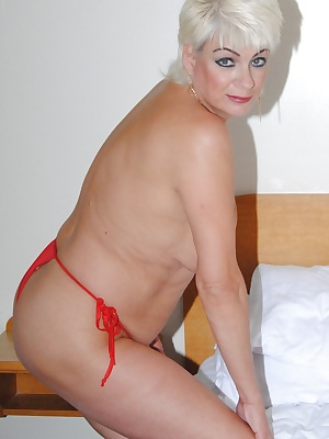 Pictures of  Dimonty in small red panties and negligee before removing everything to flash her F cup tits and wide open