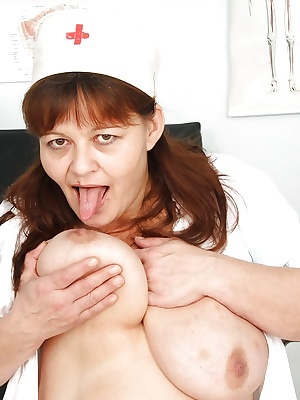 Chubby mature lady in nurse uniform uncovering her jugs and shaved twat
