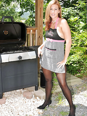 Housewife in black pantyhose posing outdoors