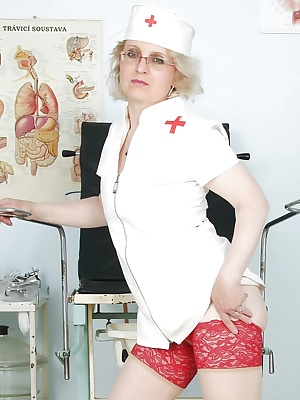 Saucy mature nurse in glasses showcasing her tits and soaking wet cunt
