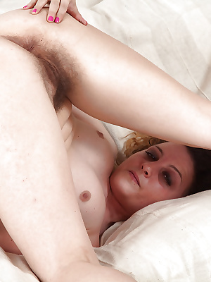 Mature woman Khalisa flashing hairy armpits and beaver on couch