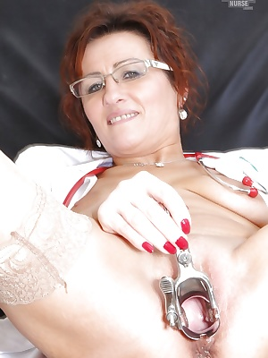 Salacious mature nurse in glasses masturbating her shaved twat