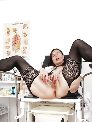 Saucy mature nurse in openwork stockings toying her trimmed twat