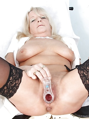 Lecherous mature nurse exposing her hairy twat and stuffing it with speculum