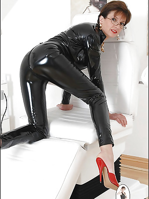Mature fetish lady in glasses posing in black latex outfit