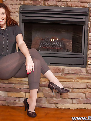 Mature lady in pantyhose posing near fireplace